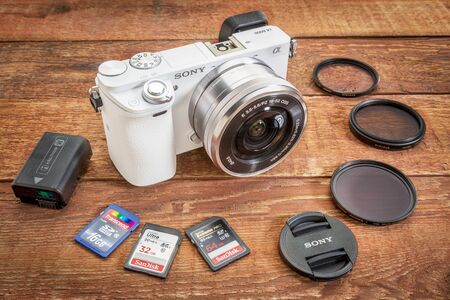 sony: FORT COLLINS, CO, USA, April 17,  2015:  Sony A6000 mirrorless digital camera with a set of filters, memory cards, lens cap and battery on a grunge barn wood table