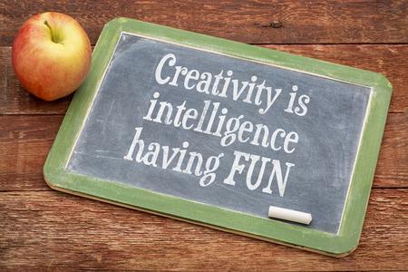 creativity: Creativity is intelligence having fun - inspirational words  on a slate blackboard against red barn wood
