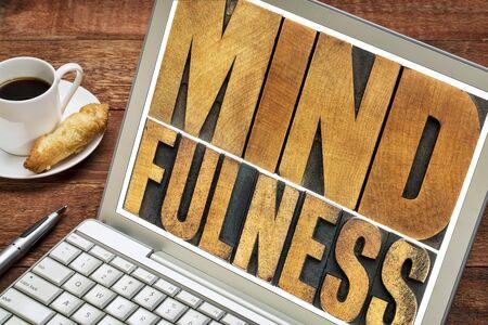 mindfulness: mindfulness woord typografie - geïsoleerde tekst in boekdruk hout soort op een laptop scherm - spiritueel concept