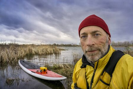 life jacket: senior paddler in life jacket with his paddleboard and lake in background, early spring scenery with stormy sky in Colorado