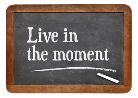 Live in the moment i- inspirational advice on a vintage slate blackboard Фото со стока