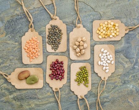 fava bean: legume abstract (fava bean, red lentils, adzuki bean, soy, mung bean,navy bean, yellow pea, French lentils) - top view of paper price tags against slate stone Stock Photo