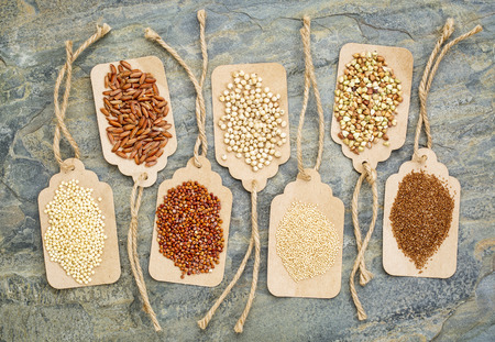 abstract of healthy, gluten free grains (quinoa, sorghum, brown rice, teff, buckwheat, amaranth, millet) - top view of paper price tags against a slate stone Stock Photo