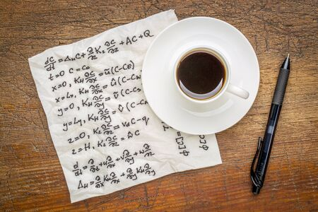derivation: mathematical equations of physics - handwriting on a napkin with a cup of coffee on a rustic wooden table
