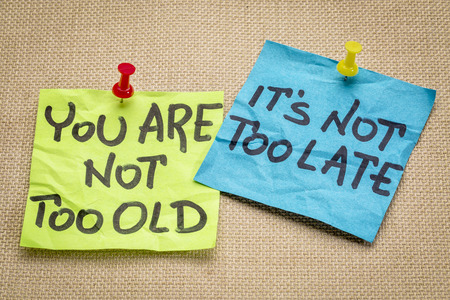 too late: You are not too old, it is not too late. Motivational advice or reminder on colorful sticky notes.
