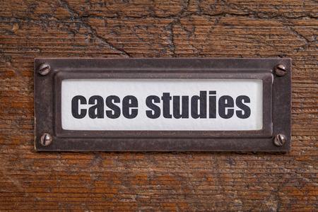 file cabinet: estudios de caso - etiqueta archivador, titular de bronce contra el grunge y madera rayado Foto de archivo