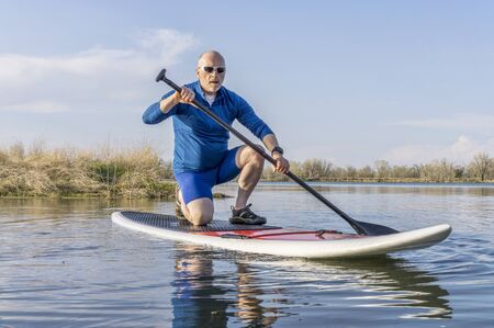 paddler: Senior male on stand up paddling (SUP) board. Early spring on calm lake in Colorado. Stock Photo