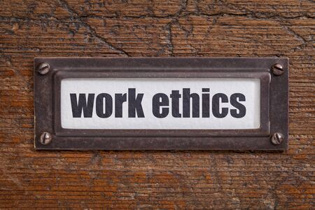 morale: work ethics - file cabinet label, bronze holder against grunge and scratched wood Stock Photo