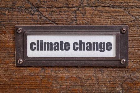 climate change  - file cabinet label, bronze holder against grunge and scratched wood
