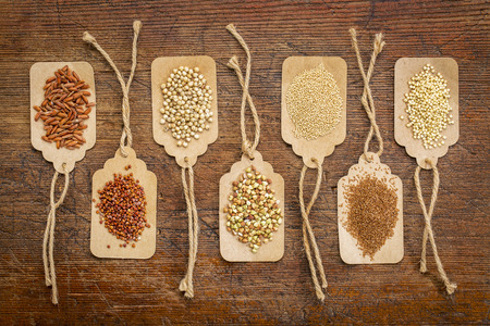 abstract of healthy, gluten free grains (quinoa, sorghum, brown rice, teff, buckwheat, amaranth, millet) - top view of paper price tags against rustic wood
