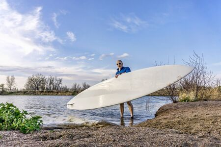 paddler: senior male paddler is launching his paddleboard on a lake, early spring in Colorado