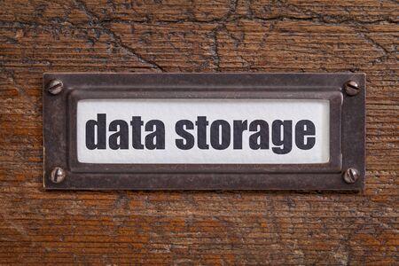 file cabinet: almacenamiento de datos - etiqueta archivador, titular de bronce contra el grunge y madera rayado Foto de archivo