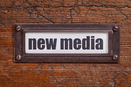 new media: new media - file cabinet label, bronze holder against grunge and scratched wood