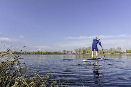 paddleboard: Senior male on stand up paddling (SUP) board. Early spring on calm lake in Fort Collins, Colorado..