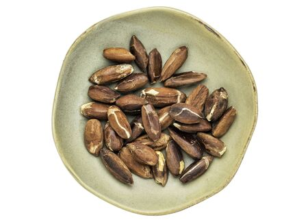 pili: roasted pili nuts grown in Philippines, top view of ceramic bowl isolated on white