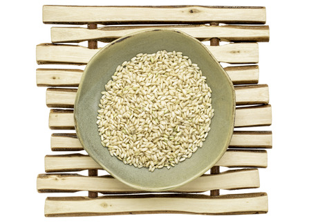 sprouted: sprouted brown rice in a ceramic bowl on a wood stick trivet