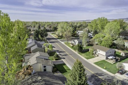 25 to 30 years old: FORT COLLINS, CO, USA - APRIL 25, 2015: Aerial view of a street in Fort Collins, a typical residential neighborhood along Front Range of Rocky Mountains in Colorado with 30 years old houses,  early spring with green trees
