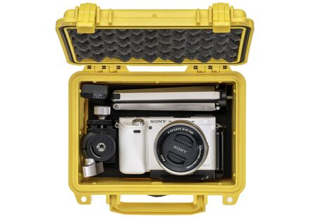 sony: FORT COLLINS, CO, USA, April 25,  2015:  Sony A6000 mirrorless digital camera with a mini  tripod and spare battery in a waterproof pelican case ready for adventure trip. Editorial
