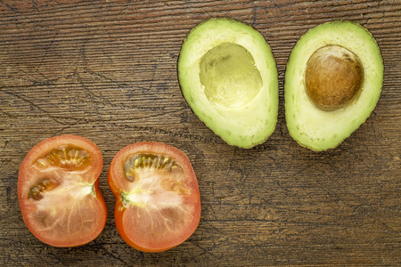 halved  half: avocado and tomato cut in half on a grunge wood with a copy space Stock Photo