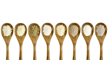 gluten free flours  collection (almond, coconut, flax meal, brown rice, quinoa, teff, potato, buckwheat) - top view of isolated wooden spoons