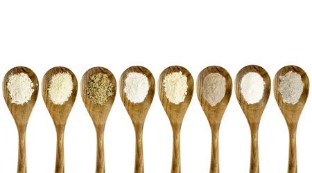 glutenvrij meel collectie (amandel, kokos, vlas maaltijd, bruine rijst, quinoa, teff, aardappelen, boekweit) - bovenaanzicht van geïsoleerde houten lepels