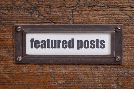 featured: featured posts   - file cabinet label, bronze holder against grunge and scratched wood Stock Photo