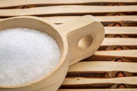 sulfate: Magnesium sulfate (Epsom salts) in a rustic wooden scoop - relaxing bath concept