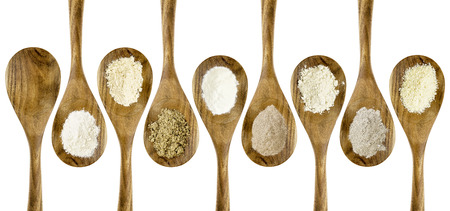 gluten free flours  set (almond, coconut, flax meal, brown rice, quinoa, teff, potato, buckwheat) - top view of isolated wooden spoons Imagens - 39431509