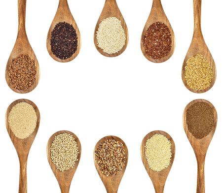 een verscheidenheid aan glutenvrije granen en zaden (boekweit, amarant, bruine rijst, gierst, sorghum, teff, zwart, rood en wit quinoa, gouden fax op houten lepels geïsoleerd op wit met een kopie ruimte Stockfoto