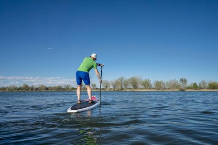 fort collins: Senior male exercising on stand up paddling (SUP) board.. Early spring on calm lake in Fort Collins, Colorado..