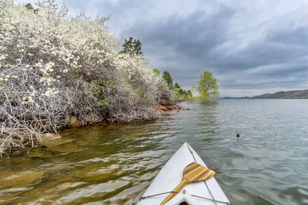 horsetooth reservoir: canoa bow with a wooden paddle on Horsetooth Rerservoir, springtime scenry with blooming bushes Stock Photo