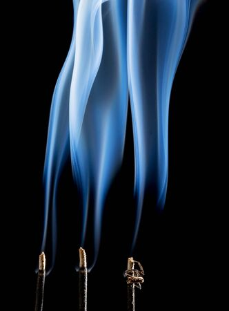 plumes: delicate smoke plumes from three  burning incense sticks Stock Photo