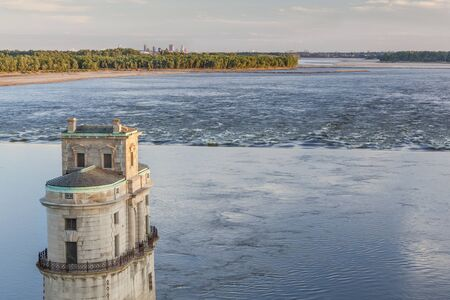 st louis: Mississippi RIver at Chain of Rocks with historical water intake tower and distant cityscape of St Louis