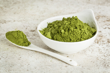 oleifera: moringa leaf powder in a small bowl with a spoon against a ceramic tile background