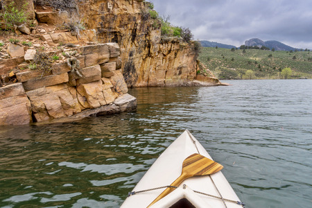 horsetooth reservoir: canoe and sandstone cliff - springtime paddling Horsetooth Reservoir near Fort Collins, Colorado