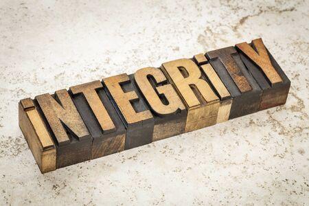 integridad: palabra integridad en el tipo de cosecha de madera de tipografía sobre un fondo baldosas de cerámica Foto de archivo
