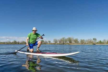 fort collins: Senior male exercising on stand up paddling (SUP) board. Early spring on a calm lake in Fort Collins, Colorado..