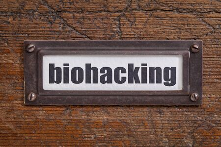 file cabinet: biohacking -  managing ones own biology using a combination of medical, nutritional and electronic techniques - file cabinet label, bronze holder against grunge and scratched wood