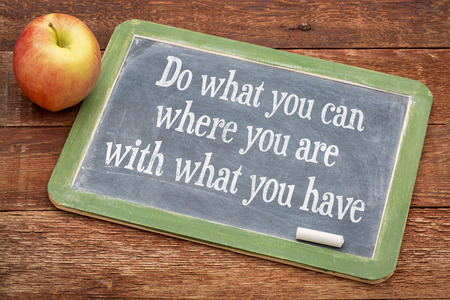 tu puedes: Haz lo que puedas, dónde estás, con lo que tienes - palabras de motivación en una pizarra pizarra contra la madera granero rojo Foto de archivo