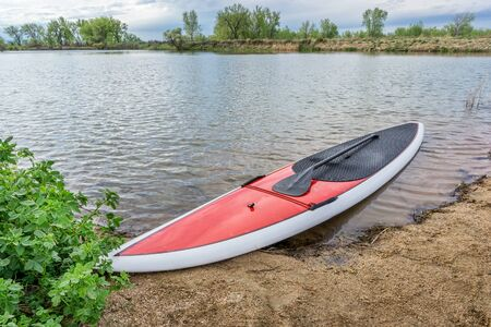 paddleboard: red stand up paddleboard on a lake shore in Colorado,. early spring