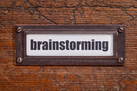 brainstorming - archiefkastlabel, bronzen houder tegen grunge en gekrast hout
