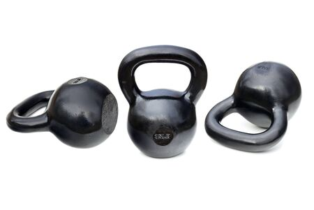 weightlifting: three black shiny 35 lb iron kettlebells for weightlifting and fitness  training isolated on white with clipping paths