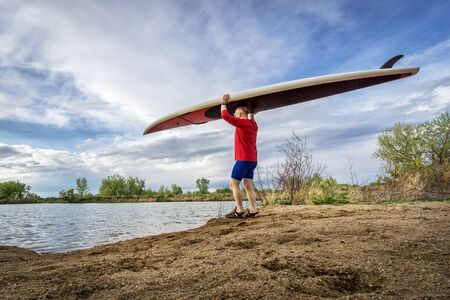 sup: senior male paddler carrying his SUP paddleboard on a lake shore in Colorado, early spring