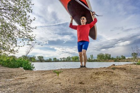 paddler: senior male paddler carrying his SUP paddleboard on a lake shore in Colorado, early spring