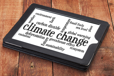 climate change: climate change word cloud on a digital tablet against rustic barn wood