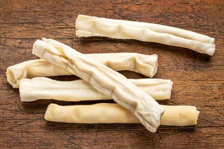 rawhide: small rawhide bones - dog treats on grunge wood background