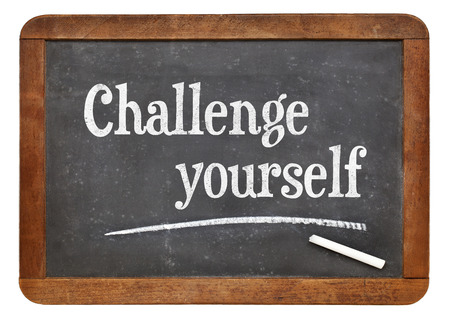 yourself: Challenge yourself - motivational text  on a vintage slate blackboard