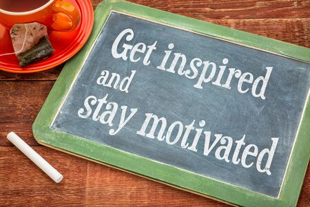 motivated: get inspired and stay motivated - motivational teax on a slate blackboard with chalk and cup of tea