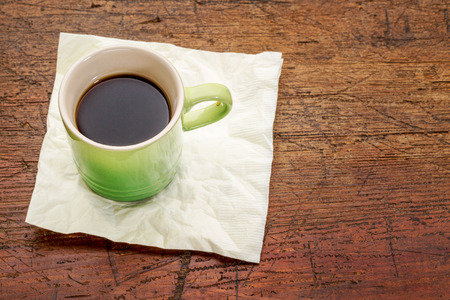 stoneware: green stoneware cup of espresso coffee on a napkin against rustic wood with a copy space Stock Photo