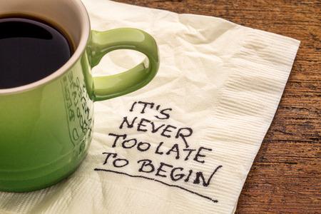 empezar: Nunca es demasiado tarde para comenzar - recordatorio de motivación en una servilleta con una taza de café